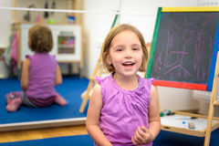 Kleines Kind zeichnet mit Farbkreide auf dem Kreidebrett Stockfotos