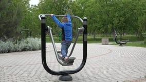 Kleines Kinderübung an der Turnhallenmaschine im Park, lokalisierter Junge mit Rückseite stock video footage