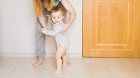 Kleines Kinderbaby, das erste Schritte machend lächelt lizenzfreies stockbild