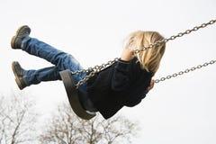 Kleines Kinderblondes Mädchen, das Spaß auf einem Schwingen im Freien hat Lizenzfreies Stockfoto