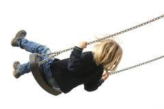 Kleines Kinderblondes Mädchen, das Spaß auf einem Schwingen im Freien hat Stockfotografie