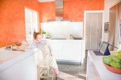 Kleines Kinderchef, der Tablette in der Küche betrachtet Stockbilder