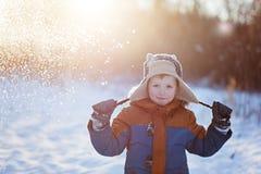Kleines Kinderdas spielen des Winters wirft oben Schnee draußen während der Schneefälle Aktive outoors Freizeit mit Kindern im Wi Stockfoto
