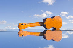 Kleines Kindergitarrenspielzeug auf Spiegel und Himmel Stockbild