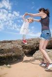 Kleines Kinderhändchenhaltenfrau, die von den Felsen springt Lizenzfreie Stockfotos