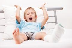 Kleines Kinderjunge mit Gipsverband auf Beinfersenbruch oder -br Stockfoto