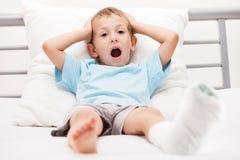 Kleines Kinderjunge mit Gipsverband auf Beinfersenbruch oder -br Lizenzfreie Stockfotografie