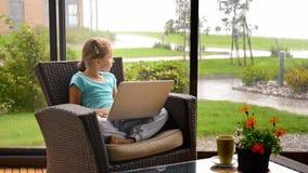 Kleines Kindermädchen, das auf der Terrasse im Lehnsessel mit Laptop sitzt stock video
