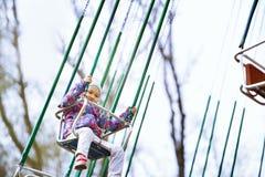 Kleines Kinderreiten auf einem chaing Schwingen lizenzfreie stockfotos