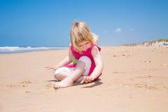Kleines Kindersitzen und -schreiben mit dem Finger auf Sand setzen auf den Strand Stockfotos