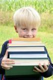 Kleines Kindertragende viele große schwere Schulbücher Stockfotos