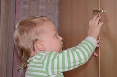Kleines Kinderversuch, zum der Tür zu Hause zu öffnen Lizenzfreies Stockbild