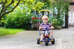 Kleines Kleinkind, das Dreirad oder Fahrrad im Hausgarten fährt Lizenzfreies Stockfoto