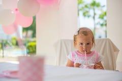 Kleines Kleinkind, das Juice From Paper Cup trinkt Stockfoto