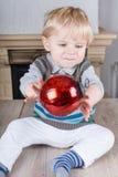 Kleines Kleinkind, das mit roter Weihnachtsbaumkugel spielt Lizenzfreie Stockfotografie