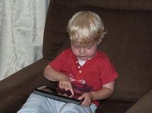 Kleines Kleinkind mit einer Tablette Stockfotografie