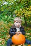 Kleines Kleinkind mit grünem Kürbis im Garten Lizenzfreies Stockbild