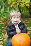 Kleines Kleinkind mit großem orange Kürbis im Garten Stockbilder