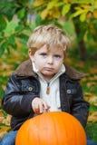 Kleines Kleinkind mit großem orange Kürbis im Garten Lizenzfreies Stockfoto