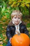 Kleines Kleinkind mit großem orange Kürbis im Garten Stockbild