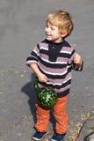 Kleines Kleinkind mit großem orange Kürbis im Garten Stockfotos