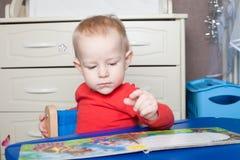 Kleines Kleinkind oder ein Babykind, das mit Puzzlespiel spielt, formt auf ein lo Lizenzfreie Stockfotografie