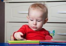 Kleines Kleinkind oder ein Babykind, das mit Puzzlespiel spielt, formt auf ein lo Lizenzfreies Stockfoto