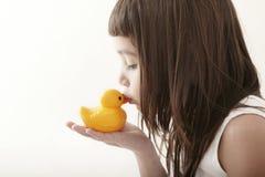 Kleines Kleinkindmädchen, das eine gelbe Badente küßt Stockfotografie