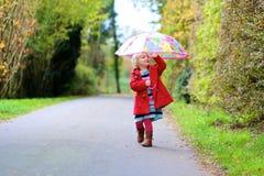 Kleines Kleinkindmädchen, das mit Regenschirm geht Stockfoto