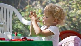 Kleines Kleinkindmädchen, das Spielwaren vom playdough herstellt Stockfotos