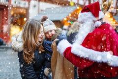 Kleines Kleinkindmädchen mit Mutter auf Weihnachtsmarkt Lizenzfreie Stockfotos