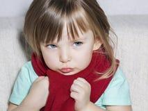 Kleines krankes Mädchen sitzt auf einer weißen Couch, die in einem roten Schal eingewickelt wird stockfoto