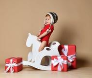 Kleines lächelndes Baby, das auf einem Schimmel, hölzernes Schaukeln sitzt stockfotografie