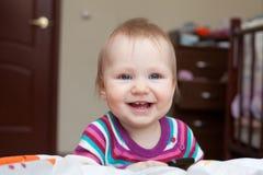 Kleines lächelndes Baby, das nahe dem Bett steht stockfotografie