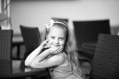 Kleines lächelndes Baby im blauen Kleid nahe Cafétabelle Stockfotos