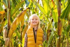 Kleines lächelndes blondes Kind, das auf einem Maisgebiet auf Bauernhof bleibt Stockbilder