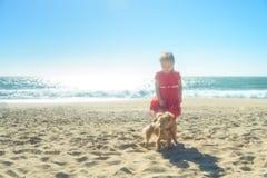 Kleines lächelndes blondes Mädchen im roten Kleid mit Hund auf dem Strand Stockfotos