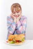 Kleines lächelndes blondes Mädchen schaut auf Hamburgern Stockbild