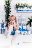 Kleines lächelndes hübsches Mädchen, das nahe bei einem Weihnachtsbaum sitzt Stockbild