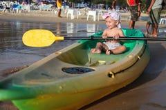Kleines lächelndes Kind, das in einem leeren Boot auf dem Strand sitzt Stockfoto