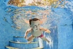 Kleines lächelndes Kind, das unter Wasser im Pool schwimmt Stockfotos