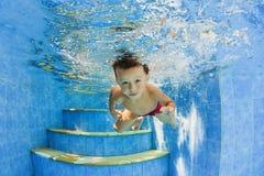 Kleines lächelndes Kind, das unter Wasser im Pool schwimmt Stockbild