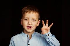 Kleines lächelndes Kind, die Jungenhand, die seine erste Milch zeigen oder die vorübergehenden Zähne fallen heraus Stockfotografie