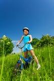 Kleines lächelndes Mädchen, das auf einem Fahrrad sitzt Lizenzfreies Stockfoto