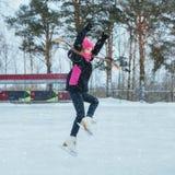 Kleines lächelndes Mädchen, das auf Eis in der rosa Abnutzung eisläuft und springt Flyng-Haare stockbild