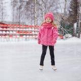 Kleines lächelndes Mädchen, das auf Eis in der rosa Abnutzung eisläuft Winter lizenzfreies stockbild