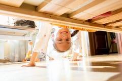 Kleines lächelndes Mädchen, das unter Bett schaut lizenzfreies stockbild