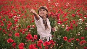 Kleines lächelndes Mädchen fängt Seifenblasen auf dem blühenden Gebiet von roten Mohnblumen, Zeitlupe stock video