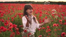 Kleines lächelndes Mädchen fängt Seifenblasen auf dem blühenden Gebiet von roten Mohnblumen, Zeitlupe stock footage