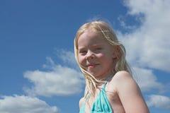 Kleines lächelndes Mädchen gegen Himmel am Sommer Lizenzfreie Stockbilder